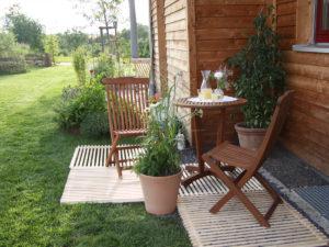 Privatgarten Sitzplatz mit ecoplate Holzrosten, Bild mit Tisch, 2 Stühlen und Stilleben sowie diversen Pflanzkübeln