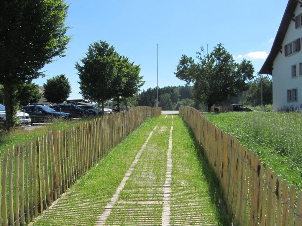 Der neue Fussweg (Naturweg) von der Juckerfarm zur Gemeinde. Links gelegen der Parkplatz, rechts gelegen das Gemeindehaus. Umsäumt wird der Weg von einem Holzzaun.